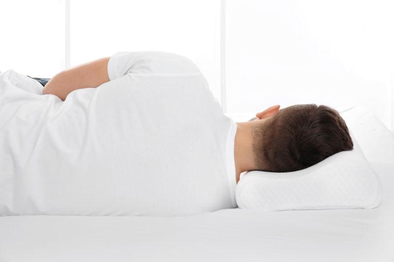 Мужчина лежит на боку на ортопедической подушке