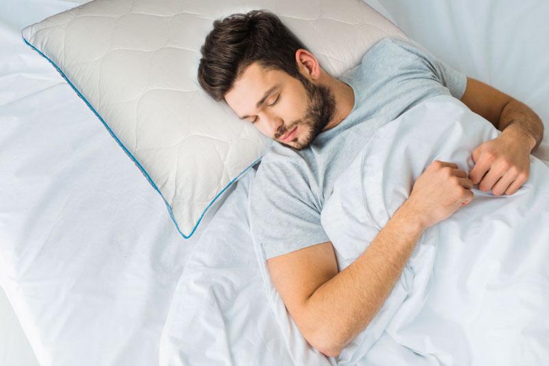 мужчина спит на анатомиечской подушке